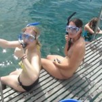 Two girls with snorkel gear getting into the sea