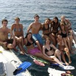 Group on back of sail boat in Caribbean