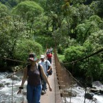Students crossing old suspension bridge in mountainous forest area