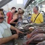 Man fileting fresh caught fish in market