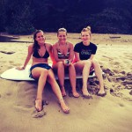 Three girls sitting on a surfboard on the beach