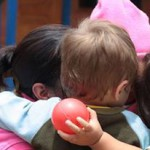 Children hugging and one with ball in hand