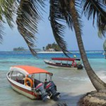 Palm tree in foreground, boats floating in caribbean sea, paradise setting