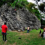 People standing next to the rock where the will climb