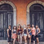Students posing in front of old doors