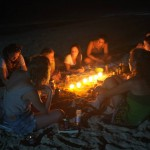 Students gathered around candles on beach