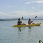 Two persons rowing in a double, yellow kayak in a bay.