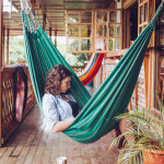 Girl reading in a hammock on a balcony