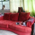Red couch with stuff in a living room