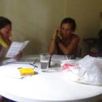 Teacher and student studying around table