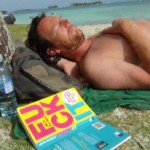 Guy sleeping under palm tree with book