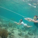 Two girls being towed under water with snorkel gear