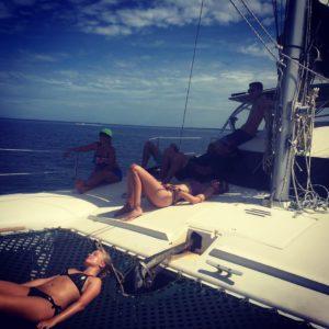 People haning out in beachwear on a Catamaran