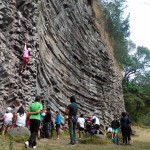 One person climbing and lots of people looking at the wall