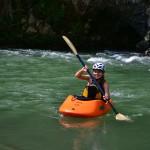 Happy girl in a orange kayak in a river