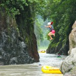 Rafter jumping from rock ledge into river